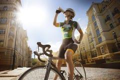 El ciclista del camino es agua potable fotos de archivo