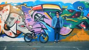 El ciclista elegante del adolescente coloca la pared cercana de la pintada con su bici en un skatepark moderno almacen de video