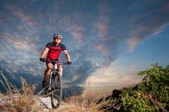 El ciclista en la bici de montaña compite con cuesta abajo en la naturaleza Imagen de archivo