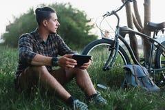 El ciclista joven del hombre del viajero se sienta en prado del verano cerca de la bicicleta, sosteniéndose en el concepto de rec Fotografía de archivo libre de regalías