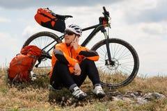 El ciclista joven en camisa anaranjada comprueba su teléfono Fotografía de archivo