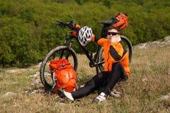 El ciclista joven en camisa anaranjada comprueba su teléfono Imagenes de archivo
