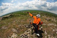 El ciclista joven en camisa anaranjada comprueba su teléfono Fotografía de archivo libre de regalías