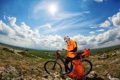 El ciclista joven en camisa anaranjada comprueba su teléfono Foto de archivo