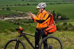 El ciclista joven en camisa anaranjada comprueba su teléfono Imágenes de archivo libres de regalías