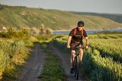 El ciclista joven monta al ciclista de la montaña en el camino en el campo en el campo Fotografía de archivo libre de regalías