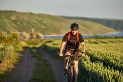 El ciclista joven monta al ciclista de la montaña en el camino en el campo en el campo Fotos de archivo