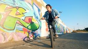 El ciclista masculino está montando una bici y está saltando en ella metrajes