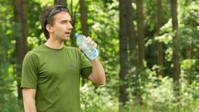 El ciclista masculino joven bebe el agua de una botella en el parque Camiseta y gafas de sol verdes metrajes