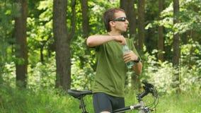 El ciclista masculino joven bebe el agua de una botella en el parque Camiseta y gafas de sol verdes almacen de video
