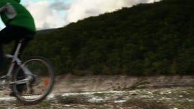 El ciclista masculino monta una bicicleta de la montaña abajo de la colina cerca del lago en otoño metrajes