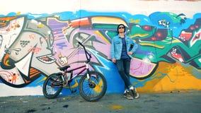 El ciclista masculino se está inclinando en una pared de la pintada con su bici que está cerca de ella metrajes