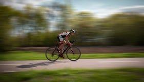 El ciclista monta en la bicicleta, efecto de la velocidad, vista lateral foto de archivo libre de regalías