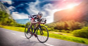 El ciclista monta en la bicicleta, efecto de la velocidad, vista lateral imagen de archivo