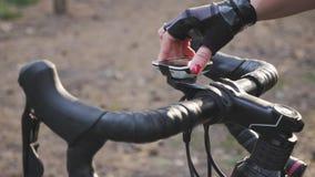 El ciclista pone el ordenador de ciclo en la bici antes de entrenar la raza Opinión del manillar Concepto de ciclo almacen de video