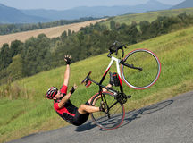 El ciclista se cae de la bici en una cuesta escarpada Fotos de archivo