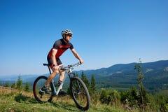 El ciclista turístico atlético en casco, las gafas de sol y el montar a caballo completo del equipo bike abajo de la colina herbo Fotografía de archivo libre de regalías