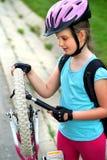 El ciclo del niño de las muchachas bombea para arriba el neumático de la bicicleta Fotografía de archivo libre de regalías