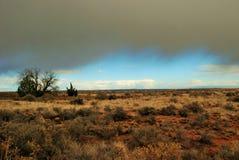 El cielo azul claro de la tarde mira a escondidas debajo de las nubes oscuras de un temporal de lluvia sobre el desierto de Arizo fotos de archivo