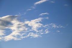 El cielo azul de la tarde con las nubes blancas las pieles del sol detrás del fotografía de archivo