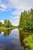 El cielo azul, las nubes y el bosque reflejaron en el agua del río Imágenes de archivo libres de regalías