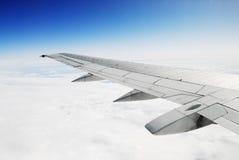 El cielo azul profundo, las nubes blancas y el aeroplano se van volando Imagen de archivo