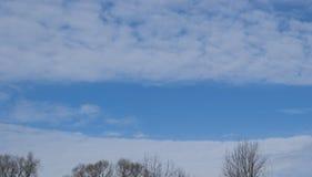 El cielo azul, rodeado por las nubes de cúmulo blancas Foto de archivo