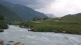 El cielo cubierto antes de la lluvia y el río rápido en montaña ajardinan metrajes