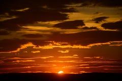 El cielo de la puesta del sol con el sol, con oro se nubla Fotografía de archivo