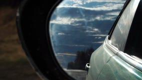 El cielo magnífico y el camino trasero reflejaron en espejo del lado del coche Cámara lenta de la conducción de automóviles metrajes