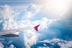 El cielo nublado y el aeroplano rojo se van volando como a través vista ventana en aircr Foto de archivo