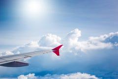 El cielo nublado y el aeroplano rojo se van volando como a través vista ventana en aircr Fotos de archivo