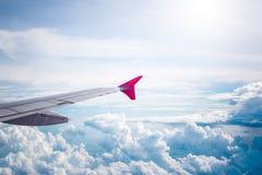 El cielo nublado y el aeroplano rojo se van volando como a través vista ventana en aircr Imagen de archivo libre de regalías