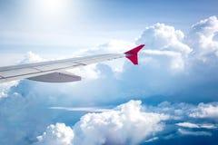 El cielo nublado y el aeroplano rojo se van volando como a través vista ventana en aircr Fotografía de archivo