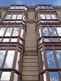 El cielo reflejado en ventanas de los edificios de una obra clásica Fotos de archivo libres de regalías