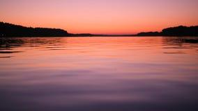 El cielo y el lago rosados coloridos asombrosos de la puesta del sol riegan la superficie Cantidad tranquila del fondo de la natu almacen de metraje de vídeo