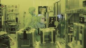 El científico de dos ingenieros en los guardapolvos de la máscara estéril va al área limpia tecnología nana de fabricación de alt metrajes