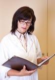 El científico de la señora sostiene el fichero con resultados del experimento Imagen de archivo libre de regalías
