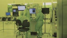 El científico de tres ingenieros en los guardapolvos de la máscara estéril va al área limpia tecnología nana de fabricación de al almacen de video