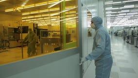El científico del ingeniero en los guardapolvos de una amapola estéril va a un área limpia tecnología nana de fabricación de alta metrajes
