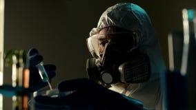 El científico en ropa protegida llena pesada realiza el experimento peligroso peligroso con la jeringuilla o el inyector varón almacen de video