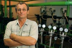 El científico en vidrios presenta cerca de los tubos con los contadores fotografía de archivo libre de regalías