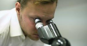 El científico está mirando a través del microscopio y está escribiendo datos en la tableta almacen de video