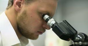 El científico está mirando a través del microscopio y está escribiendo datos en la tableta metrajes