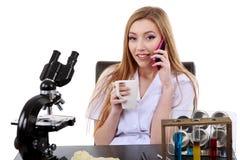El científico hermoso de la mujer en laboratorio con café habla el teléfono Fotografía de archivo