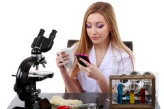 El científico hermoso de la mujer en laboratorio con café habla el teléfono Fotografía de archivo libre de regalías