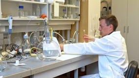 El científico joven conduce experimentos químicos con los líquidos en el laboratorio almacen de video