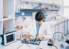 El científico joven repara el dispositivo electrónico Fotografía de archivo