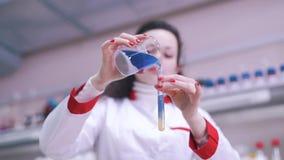 El científico mezcla líquidos en laboratorio almacen de video