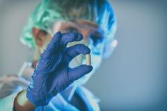 El científico que trabaja en un laboratorio sostiene una píldora Foto de archivo libre de regalías